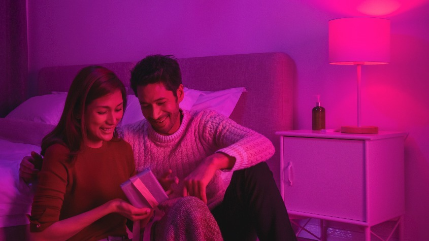 Couple relaxing in a pink-lit bedroom