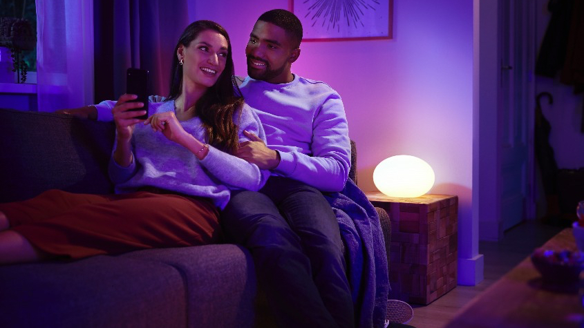 Couple talking and sitting on a sofa in a purple-lit living room